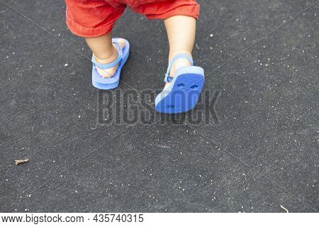 Baby's Foot Wearing Red Pants And Blue Beach Sandals On A Black Background And Copy Space.