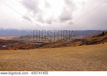 Hilly Desert Steppe At The Foot Of A High Mountain Range In Early Autumn.