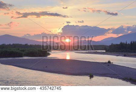 The River Bank In The Altai Mountains Under The Golden Evening Sky. Siberia, Russia