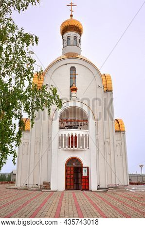 Achinsk, Siberia, Russia -09.01.2021: Entrance To The White Orthodox Church Under Golden Domes Under