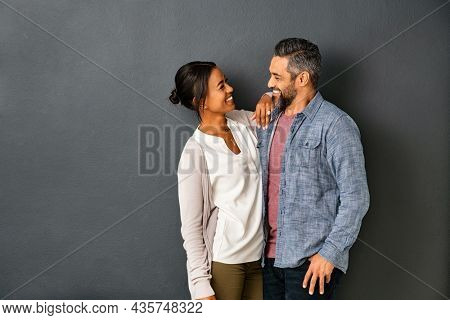 Happy mature indian couple embracing and looking at each other against gray background. Mid adult multiethnic couple in love standing against grey wall. Middle eastern man fall in love of his girl.