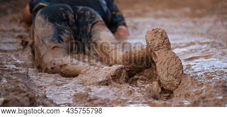 Mud Race Runners. Crawling, Passing Under A Barbed Wire Obstacles During Extreme Obstacle Race. Focu
