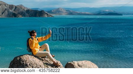A Female Traveler Is Talking On A Video Call Against The Background Of The Sea, Panorama. A Traveler