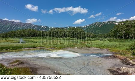 A Hot Spring In The Caldera Of An Extinct Volcano. Multicolored Stripes Of Thermophilic Organisms Ar