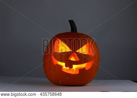 Jack o lantern Halloween pumpkin with carved funny face on gray background