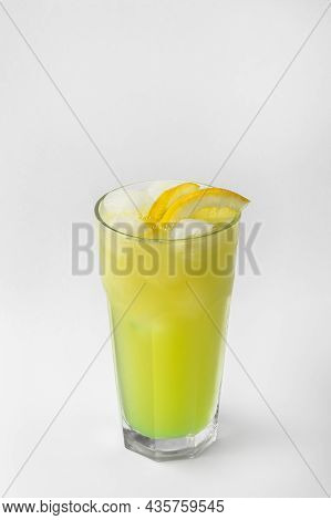 Beautiful Transparent Glass Of Summer Drink. Green And Yellow Lemonade With Ice And Lemon Isolated O