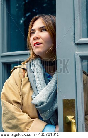 Young Caucasian Woman In Coat And Blue Scarf Walking Out The Door And Looking Around. Fashionably Dr