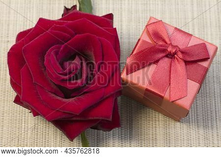 Gift Or Present Box Wrapped In Red Paper And Rose Flower On Gray Table Top View. Flat Lay Styling