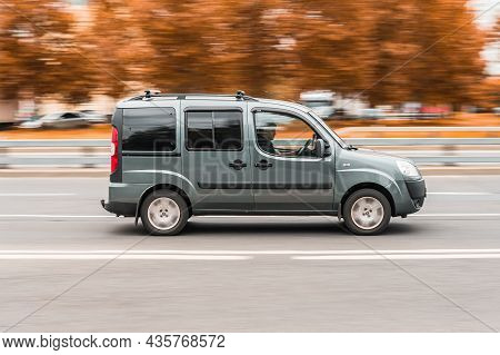Fiat Doblo Rides On The City Road With Autumn Trees Background. Family Mpv Fiat Doblo In Motion. Mos