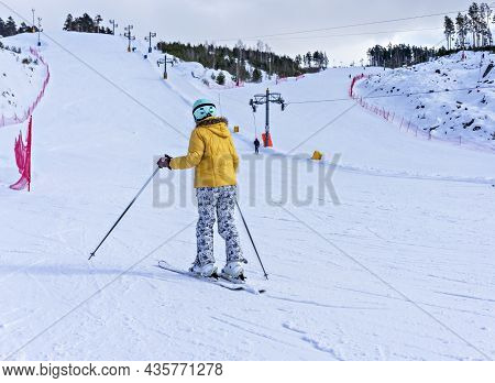 Rear View Of Young Woman In Yellow Jacket And Ski Helmet Downhill Skiing On A Mountain Slope, Winter