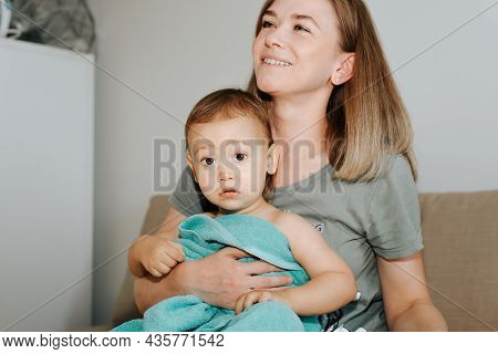 Smiling Young Mother Wiping Her Baby With Towel After Bathing At Home Indoors. Mom And Cute Little B