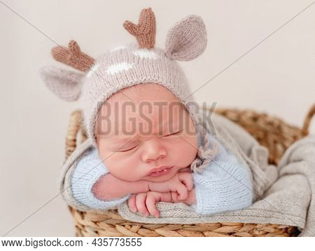 Portrait of newborn baby boy wearing knitted hat with deer horns sleeping on his tummy and holding tiny hands under his cheeks. Adorable infant child napping