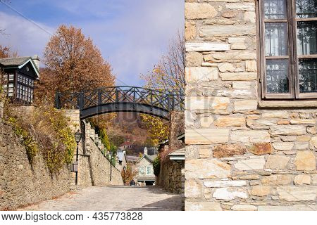 Black Metal Suspension Bridge On An Autumn Street In Nymfaio Greece. Wrought Iron Grates, Wooden Fra