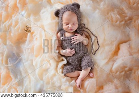 New Born Sleeping Baby In A Bear Costume. Beautiful Posing Of A Newborn Baby In A Hat With Ears And