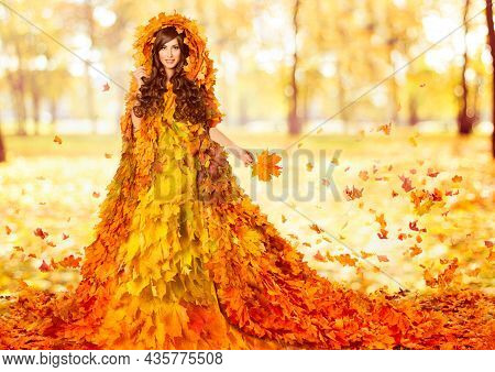 Autumn Fashion Model In Maple Leaves Orange Dress. Fantasy Woman In Creative Floral Gown Over Sunshi