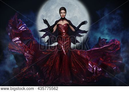 Halloween Witch Over Full Moon Night Background. Mysterious Woman In Red Long Fluttering Dress And C