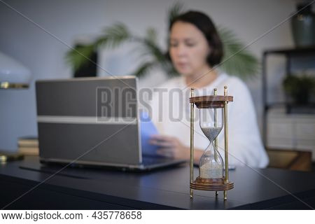 Woman Working Behind A Laptop Out Of Focus, Focus On The Hourglass.