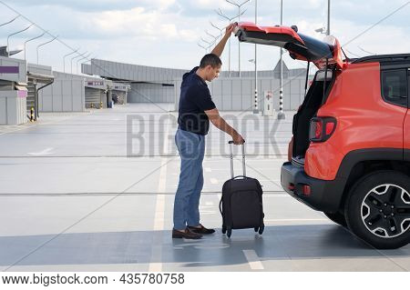 A Man Puts His Suitcase In The Trunk Of A Car In An Airport Parking Lot. Travel, Vacation Concept