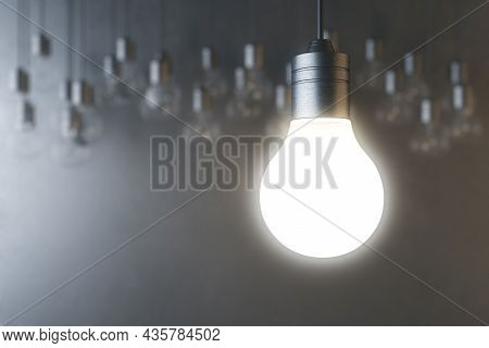 Glowing Light Bulb On Blurry Concrete Wall Backdrop. Idea, Innovation, Solution And Invention Concep