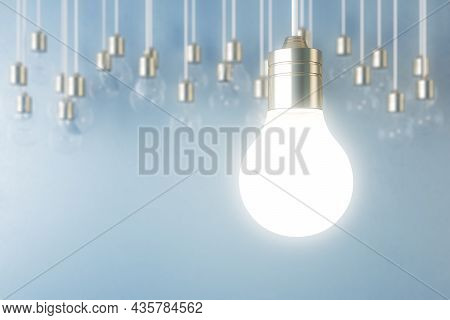 Glowing Light Bulb On Blurry Blue Wall Backdrop. Idea, Innovation, Solution And Invention Concept. M