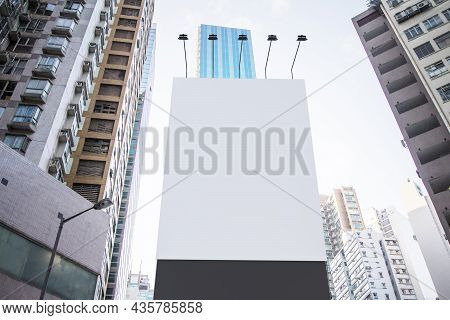 Empty White Rectangular Billboard In City With Bright Sky And Daylight. Advertisement And Commercial