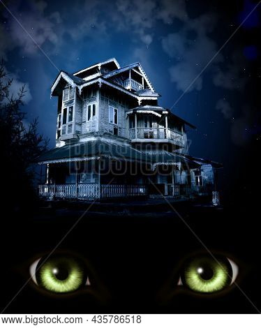 Haunted house on night sky background. Old abandoned house, burning green monster eyes and mysterious landscape. Photo toned in blue color
