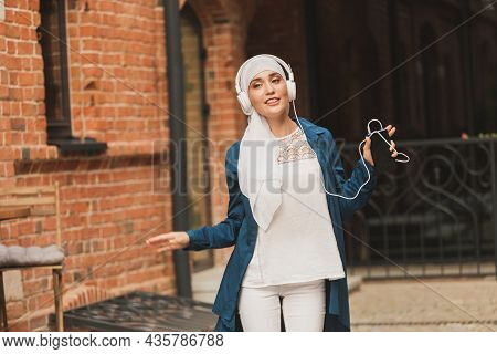 Portrait Of Young Arabian Muslim Woman Listening Music With Headphone And Dancing. Feminism, Woman I