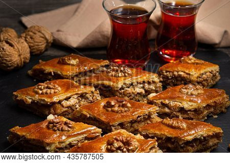 Honey Baklava With Walnuts On Black Slate. Portions Of Oriental Sweets. Turkish Sugary Pieces. Tea P