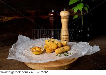 A Portion Of Cheese Sticks, Served On A Wooden Board With Mustard. Bar Deep Fried Food. Shot In The