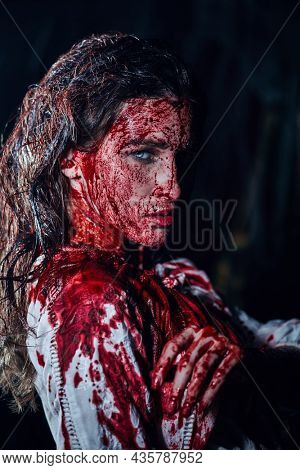 Portrait of a girl drenched in blood in a dark gloomy room. Horror, thriller. Halloween. Vampires.