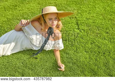 Portrait of a lovely blonde girl in a white summer dress and wide-brimmed straw hat having a rest  on a green lawn on a sunny day. Summer vacation and fashion. Copy space.