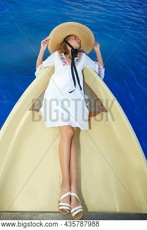 Portrait of a stunning tanned blonde girl in a stylish light white dress and a wide-brimmed straw hat going on a boat. Summer vacation and fashion.