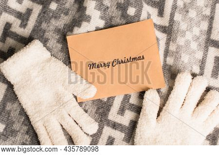 Top View Of Warm Gloves And Greeting Card With Merry Christmas Lettering On Grey Blanket With Orname