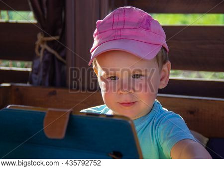 Kid Carefully Looks At The Smartphone Screen. The Child Is Fascinated By Games And Apps On The Phone