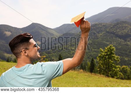 Man Throwing Paper Plane In Mountains On Sunny Day