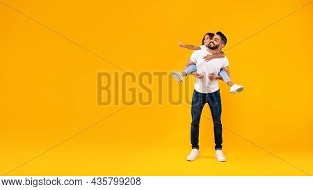 Middle-eastern Father Carrying Daughter Having Fun Over Yellow Background, Panorama