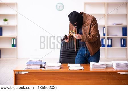 Young man in balaclava stealing information from the office