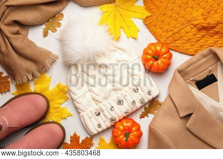 A Set Of Warm Autumn-winter Clothes With Fallen Leaves And Pumpkins On A White Background. Flat Lay