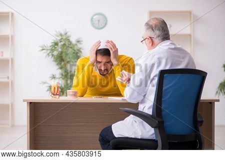 Young man visiting experienced male dentist