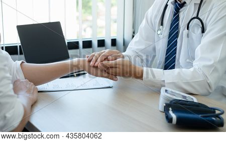 The Man Doctor Uses A Friendly Hand To Hold The Patient's Hand To Give Confidence And Show Care Abou