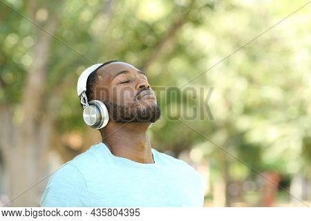 Happy Black Man Listening Audio Guide And Breathing Fresh Air In A Park