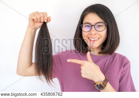 Portrait Of Attractive Asian Woman Holding A Ponytail Cutting Hair For Donation. Usable Hair Can Tur
