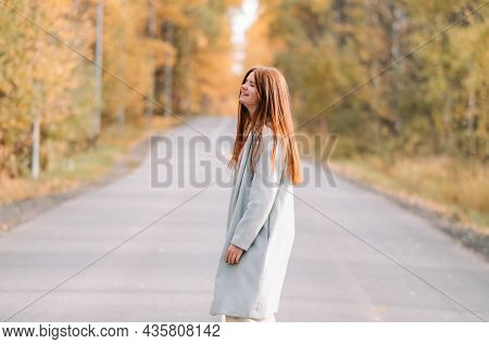 Beautiful Red-haired Girl In The Autumn Forest. Portrait Of A Young Woman In The Park.