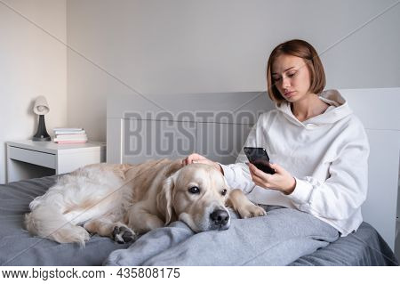 An Upset Girl Sits With A Dog On The Bed, Looks At The Phone And Listens To Sad Music. Teenage Depre