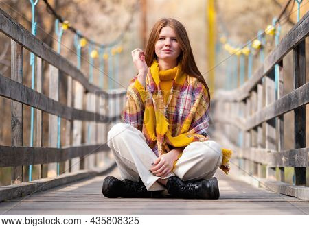 A Red-haired Girl Sits On A Wooden Bridge In An Orange Sweater And Looks At The Autumn Sun. Relaxed