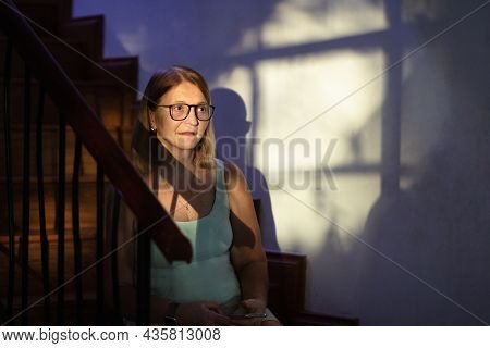 Sad Stressed Woman With Telephone. Depression And Anxiety. Senior Female Sitting On Stairs Step In D