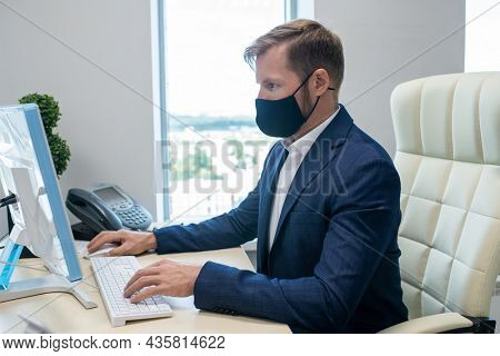 Young Caucasian white collar worker working in front of computer in office