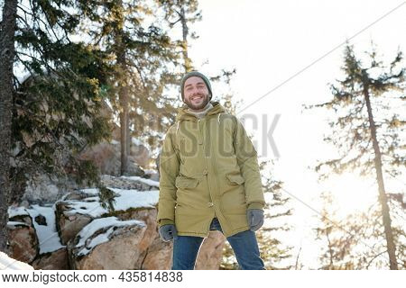 Happy young man looking at you while enjoying frosty winter day in the forest