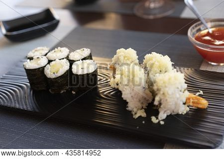 Traditional Japanese Rolls Sushi With Cucumbers And Rolls Sushi With Shrimps Fried On Black Plate At