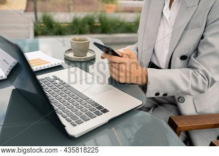Hands of young elegant female broker texting in smartphone over laptop keypad